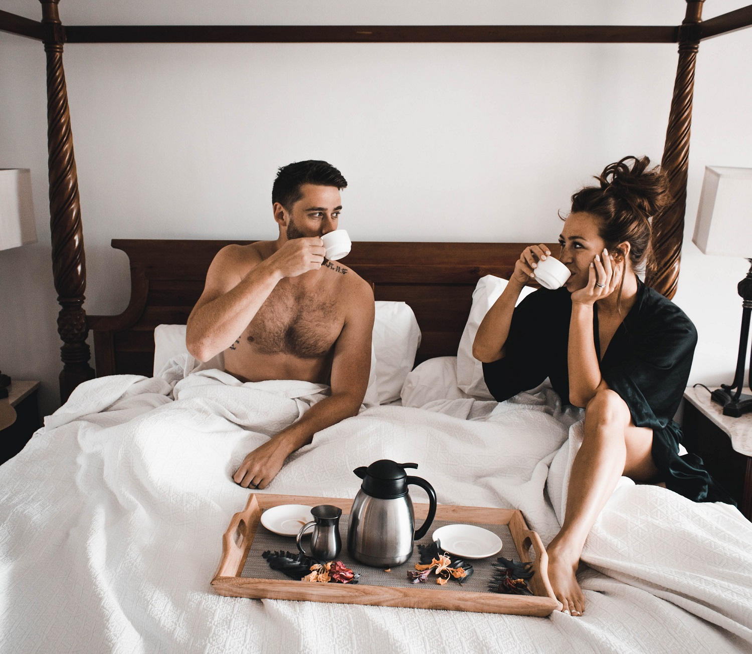 A man and woman in bed, eating oysters
